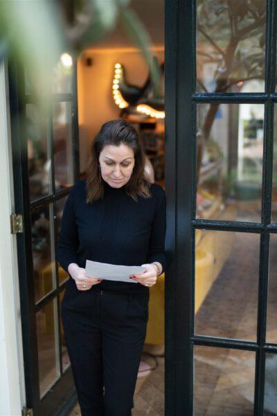 Janneke in een deuropening een dossier lezend